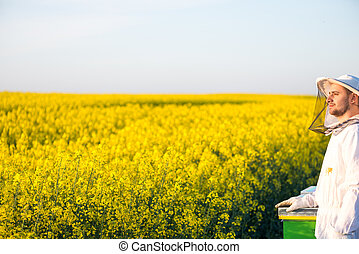Proud apiarist, on the rapeseed field, near his hives,...
