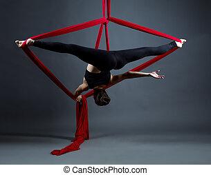 Studio shot of acrobat performs on hanging ribbons