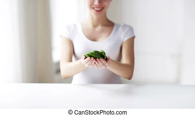close up of young woman showing spinach - healthy eating,...
