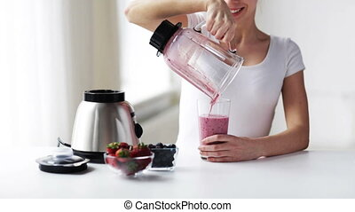 smiling woman with blender jar pouring milk shake - healthy...