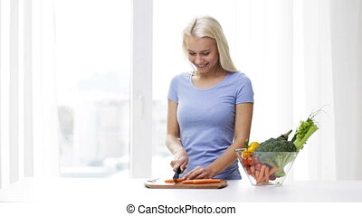 smiling young woman chopping vegetables at home - healthy...