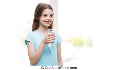 happy smiling little girl drinking water at home - people,...