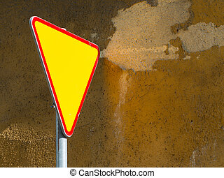 Give way sign - yield sign - against rough mustard wall...