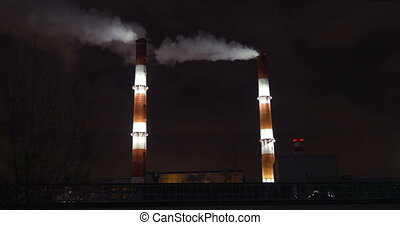 Smoking factory pipes in the city at night - Two huge...