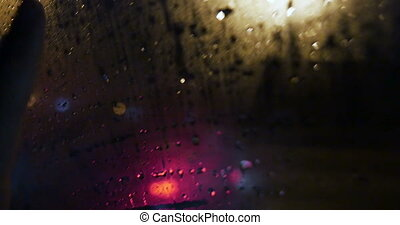 View of city through wet and weepeing car window - Close-up...