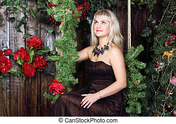 Beautiful young woman sits on swing and looks up in room with Christmas decoration