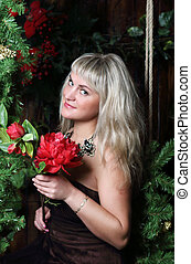 Beautiful young woman sits on swing with red flower in room with Christmas decoration