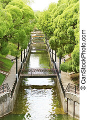 Summer sunny park with green trees, channel, beautiful bridges and lanterns
