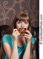 Young beautiful woman drinks coffee from gilt cup on couch in room