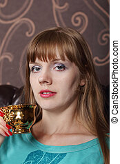 Young beautiful woman holds in hand cup of coffee on couch in room