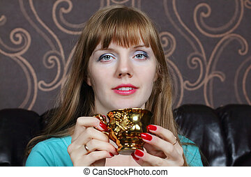 Young beautiful woman smiles and holds gilt cup on couch in room