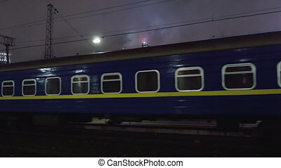 Passenger train arriving to station in the evening -...