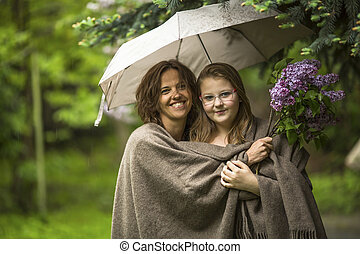 Woman with her daughter standing in the Park under an...
