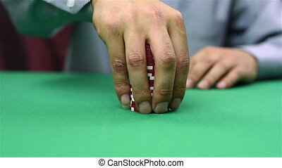 dealer collects red poker chips from the table