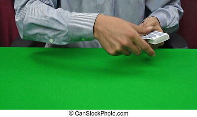 dealer dealing cards by tossing them across poker table