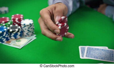 poker player with chips - poker player touches the chips in...
