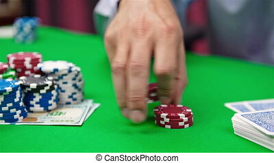 hand collects red poker chips on green table