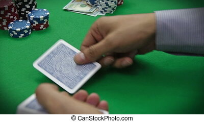 poker dealer distributes cards on the green table