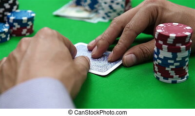 poker player looks at card