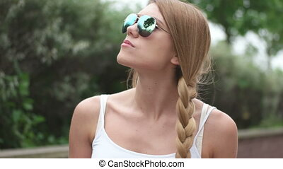 pretty girl walking wearing sunglasses and plait hair