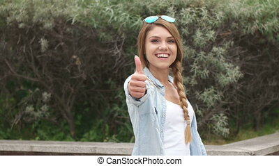 young pretty blonde girl showing thumb up and down