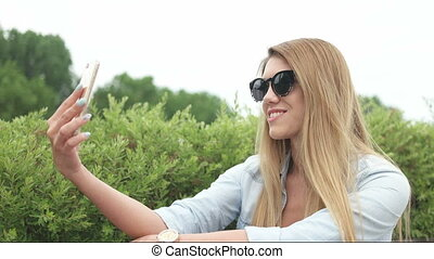 pretty woman walking then stopping for a selfie