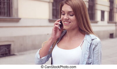 happy young woman walking and speaking over the phone