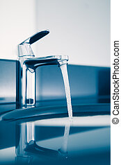 faucet with flowing water, blue tone