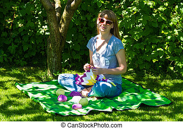 young wooman with needlework in garden