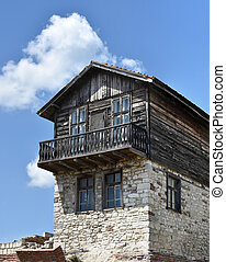Old house from wood and stone with terrace
