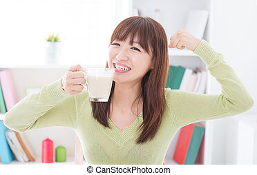 Asian female drinking milk and showing strong arm - Portrait...