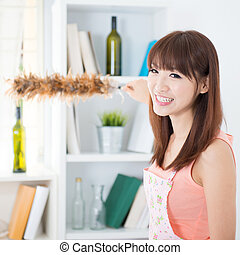 Housecleaning - Happy Asian housewife with apron cleaning...
