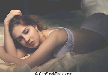 Woman in white underwear lying sexy in bed. Vintage toning....