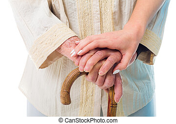 Senior woman in need - Elderly womans hands holding a wooden...