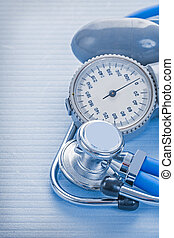 bluud pressure monitor and stethoscope on blue background