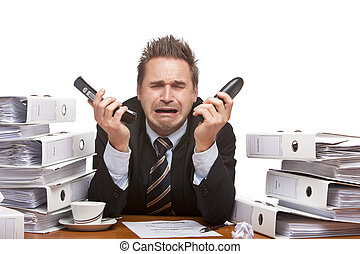 Young businessman is sitting on desk, holding two telephones...