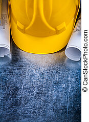 Pair of construction plans and hard hat on metallic background b