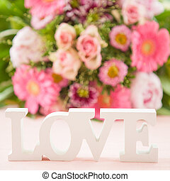 LOVE in front of flower bouquet - LOVE in wooden letters in...
