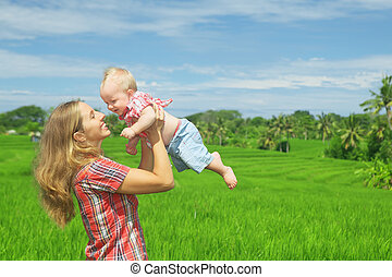 Mother with son on green rice field - Happy mother tossing...
