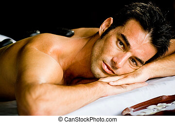 Man at Spa - A good looking man lying on a massage bed with...