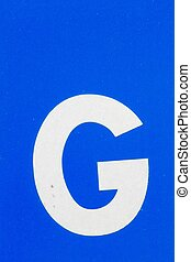 white letter G from traffic road sign - closeup white letter...