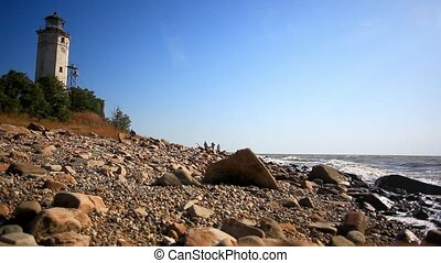 People walking far afield on a beach towards lighthouse with...