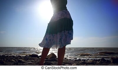 Young romantic woman alone standing on stone beach and looks in far afield