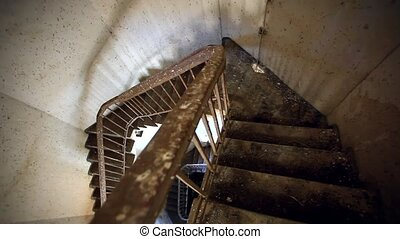 Dark spiral staircase with window into a lighthouse. Down the stairs