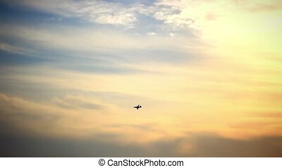 Military airplane at flying on the speed in sunset sky