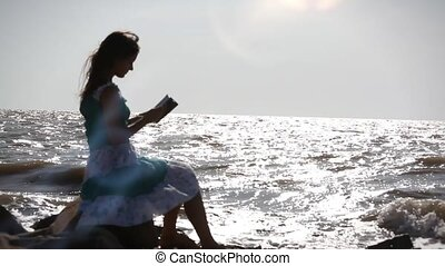 Blurred silhouette of Young romantic woman in dress sitting...