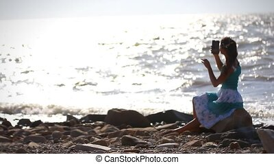 Young romantic woman in dress sitting on stone, talking...