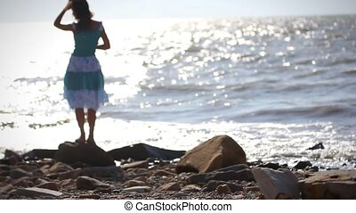 Young romantic woman in dress standing on stone and takes a...