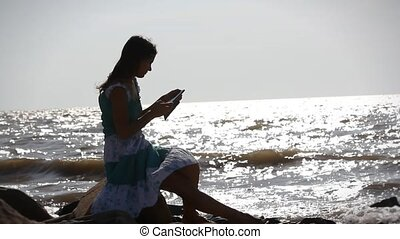 Young romantic woman in dress sitting on stone and uses phone on the beach. Sunlight reflected in sea