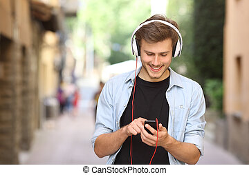 Guy walking and using a smart phone with headphones - Happy...